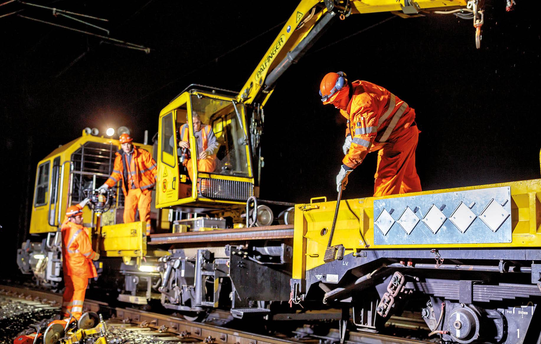 Bauarbeiter auf einer Gleisbaumaschine