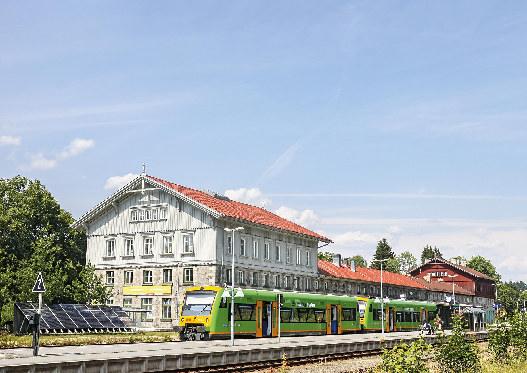 Bahnhofsgebäude, davor ein Regionalzug, seitlich eine Solaranlage