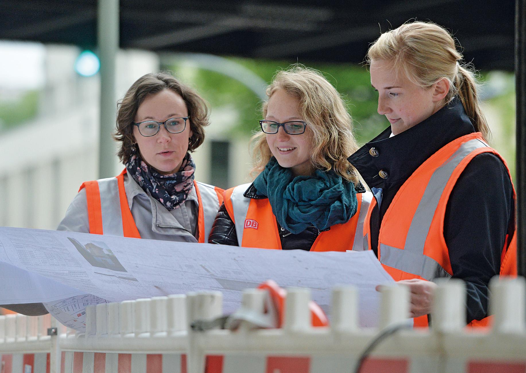 Drei junge Bahningenieurinnen an einer Baustelle