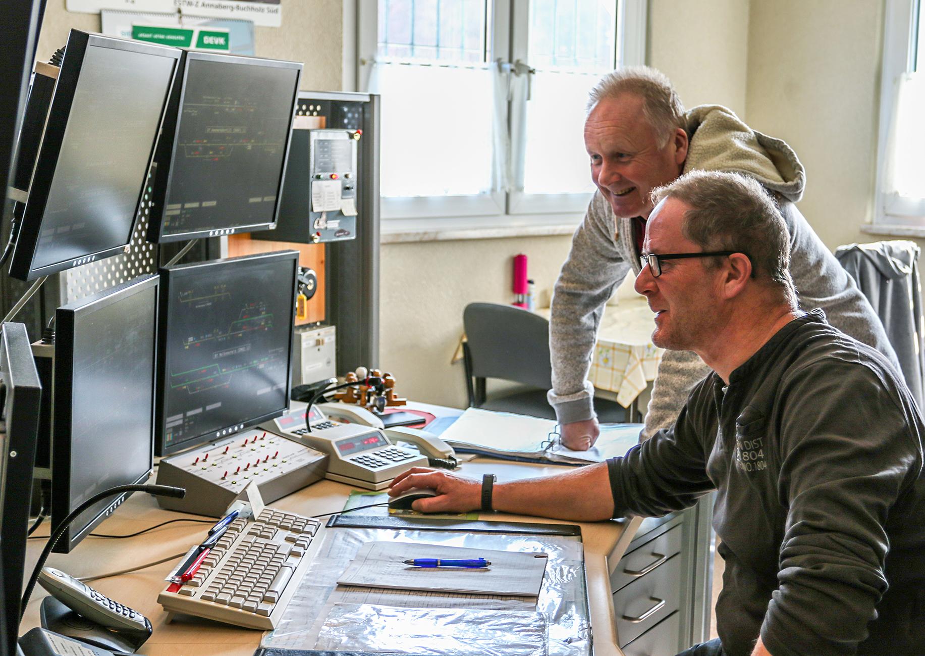 Zwei Mitarbeiter im digitalen Stellwerk, Arbeitsplatz mit mehreren Bildschirmen