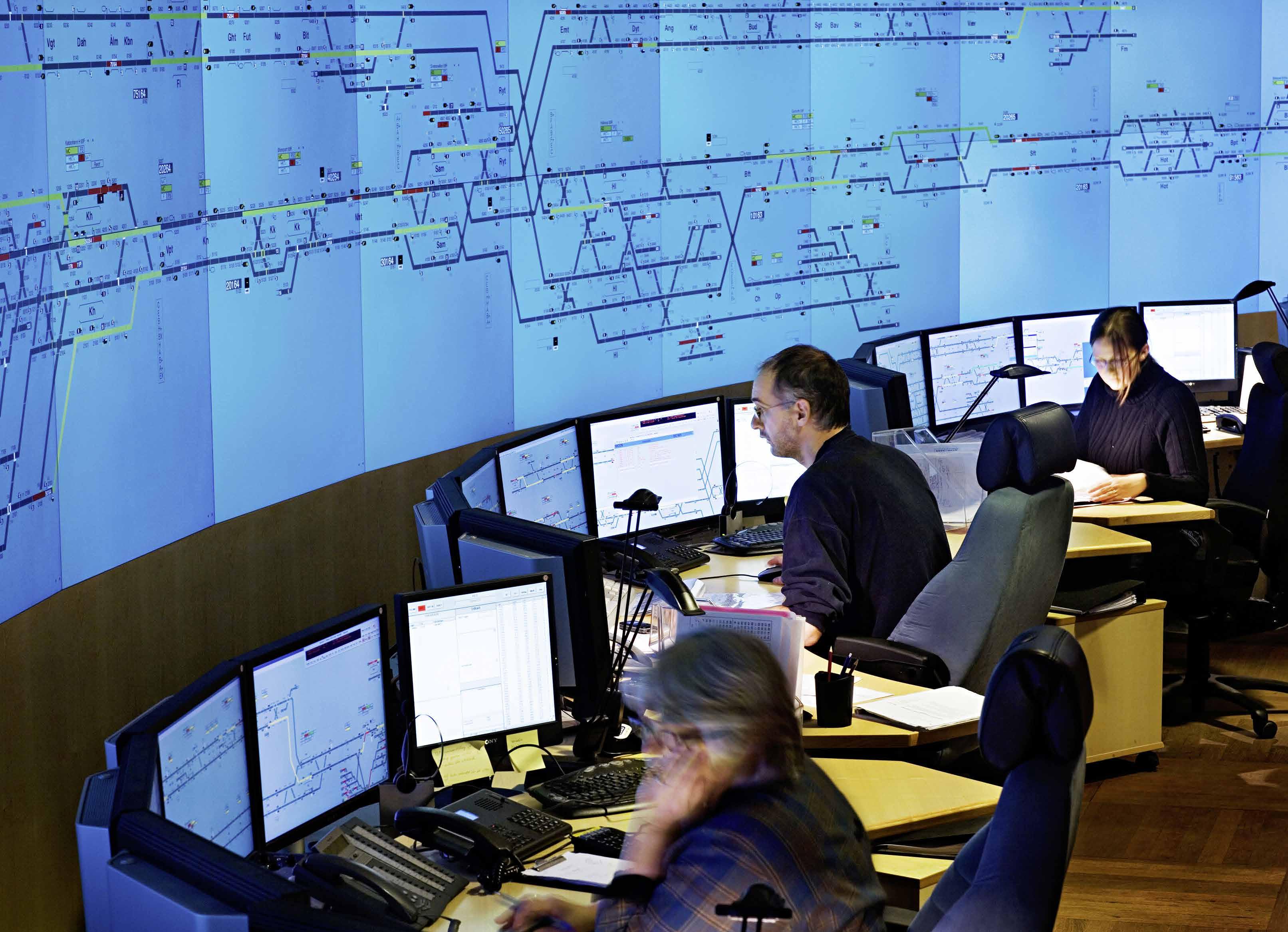 Personen vor Bildschirmen sitzend, großes Streckenband an der Wand
