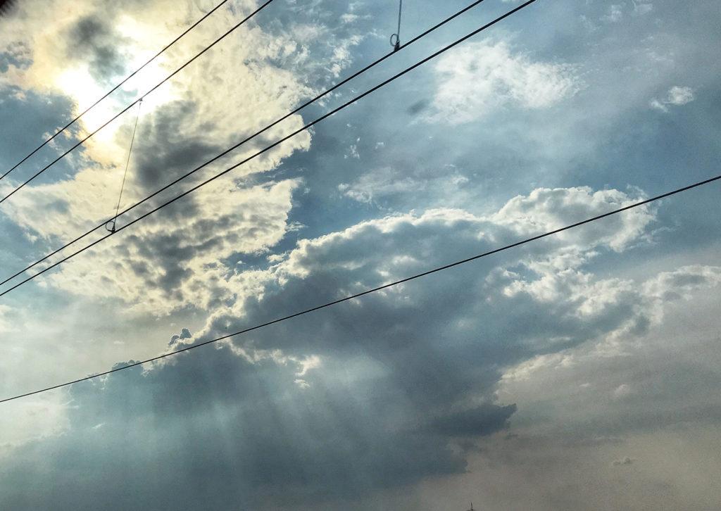 Elektrische Oberleitung einer Bahnstrecke vor bewölktem Himmel