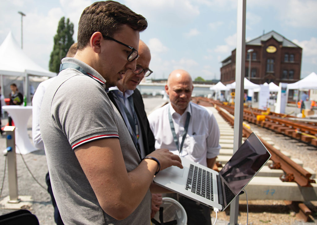 Drei Männer am Baugleis mit laptop