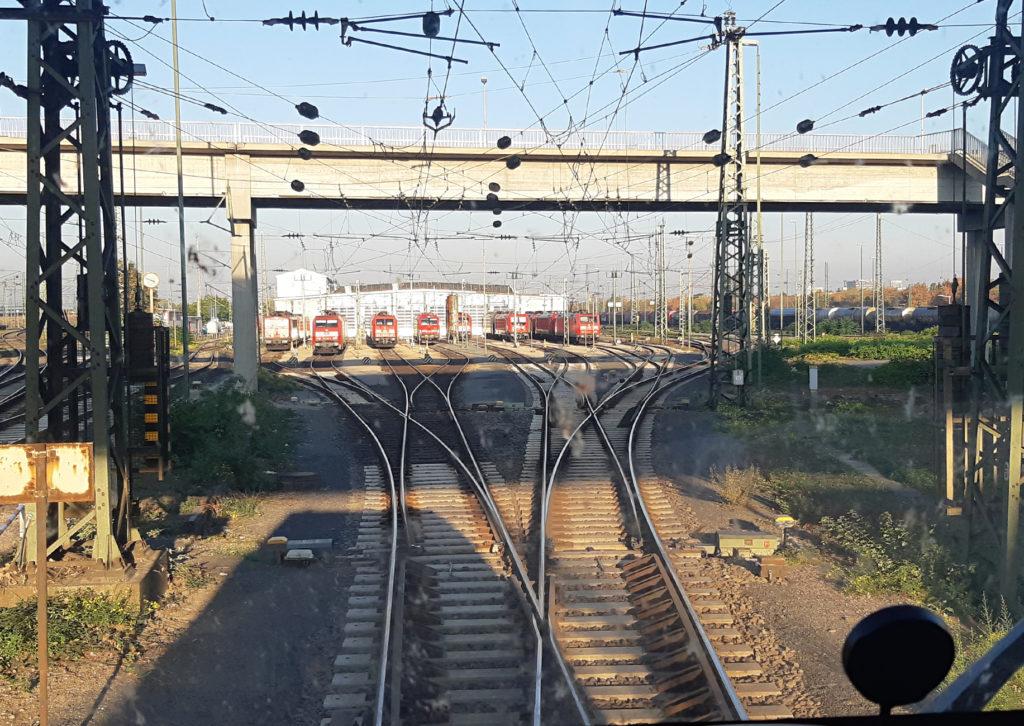 Blick auf Fahrweg und eine Brücke aus Sicht des Lokführers bei Einfahrt in einen Bahnhof in Mannheim