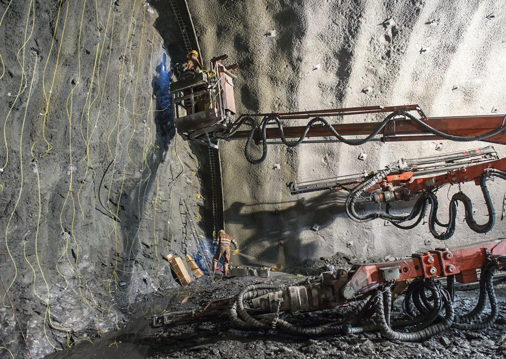 Ein Arbeiter auf einer Hebebühne vor einer Tunnelwand