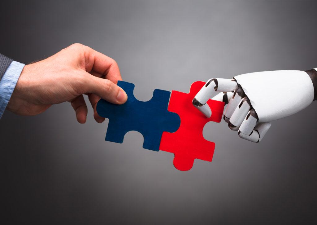 eine künstliche und eine menschliche hand mit zwei puzzleteilen