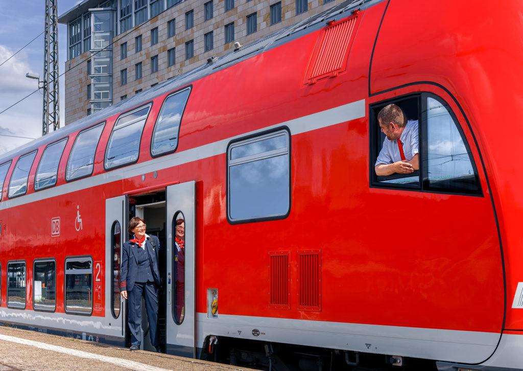 Kundenbetreuerin und Triebfahrzeugführer eines Regionalzugs am Bahnsteig im Gespräch