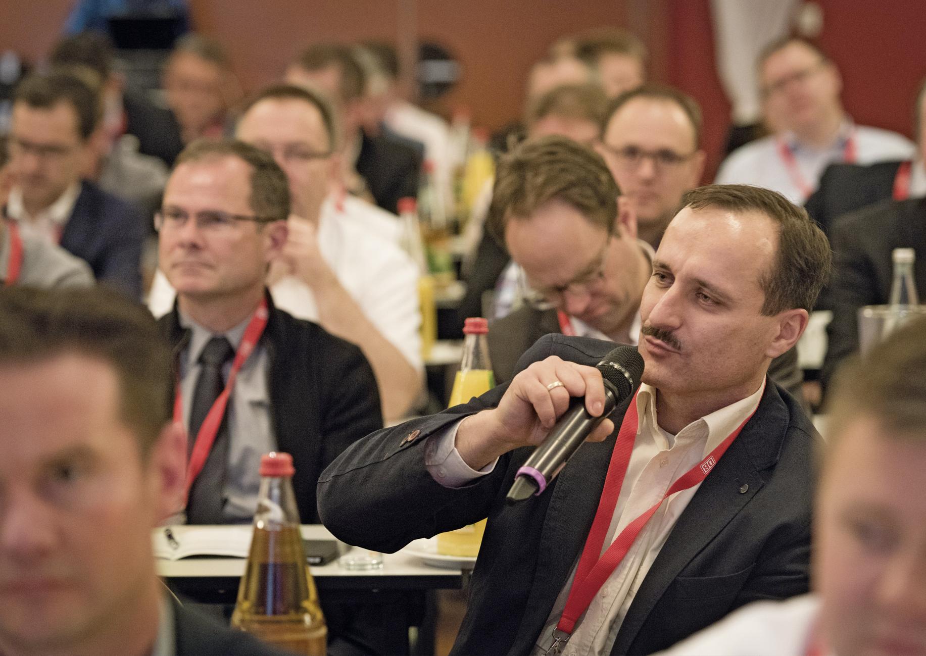 Teilnehmer auf einem DB-Fachkongress mit Mikrofon