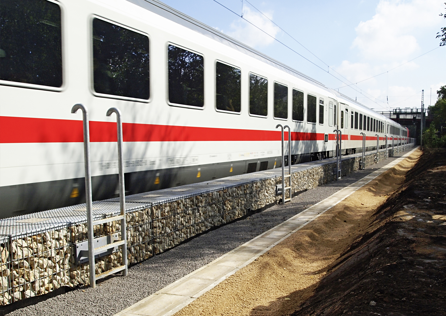 Zug fährt an Schallschutzwaand vorbei