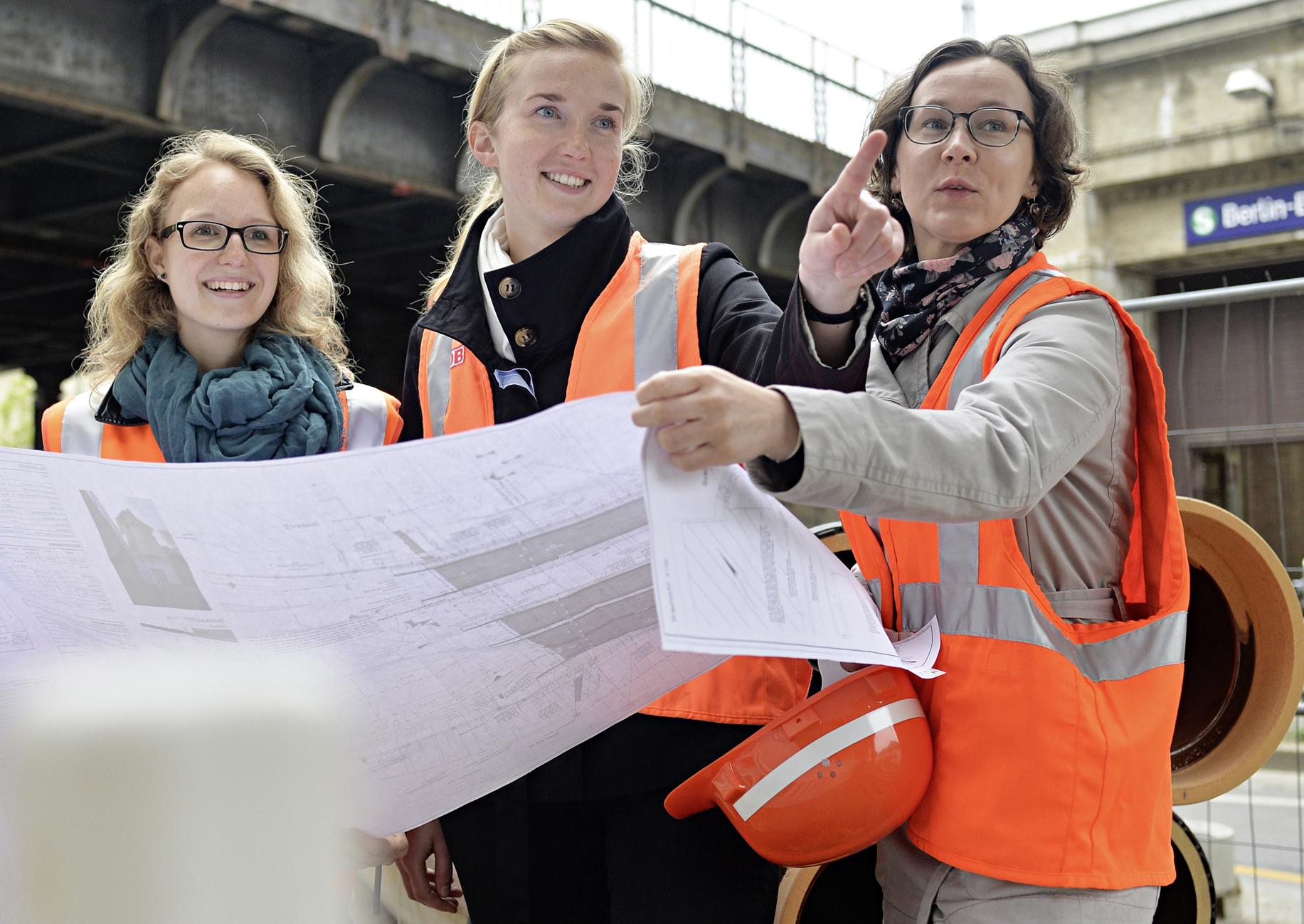 Weibliche Bahningenieure mit technischen Unterlagen an einem Bahnhof