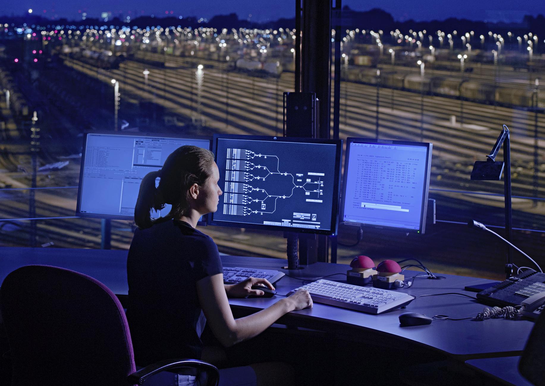 Mitarbeiterin hinter Bildschirmen in einer DB-Betriebszentrale