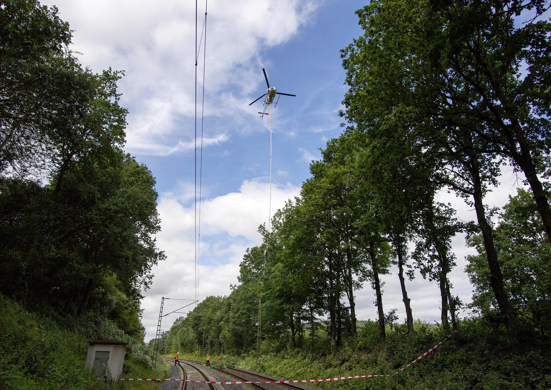 Helikopter mit einer meterlange Säge über Bahngleisen
