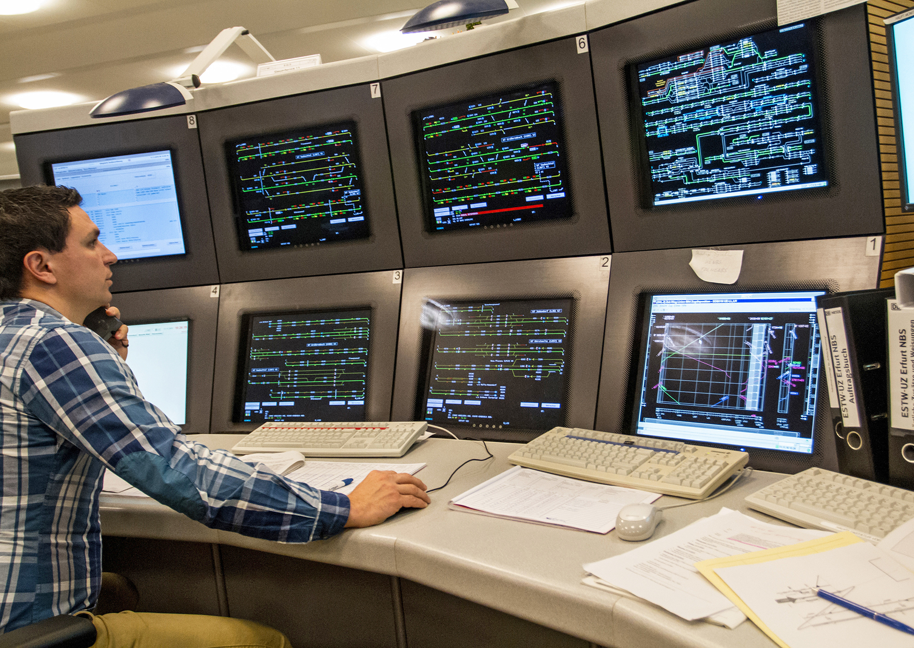 Jeweils vier Bildschirme übereinander mit Mitarbeiter davor