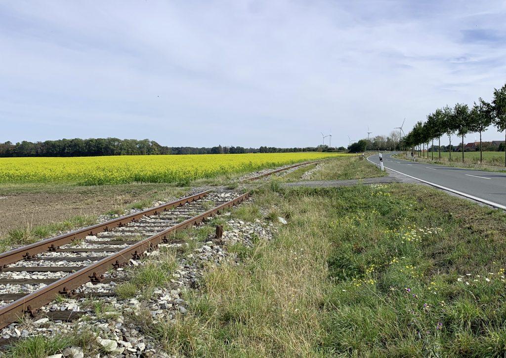 Landschaft mit Gleisen neben einer Landstraße