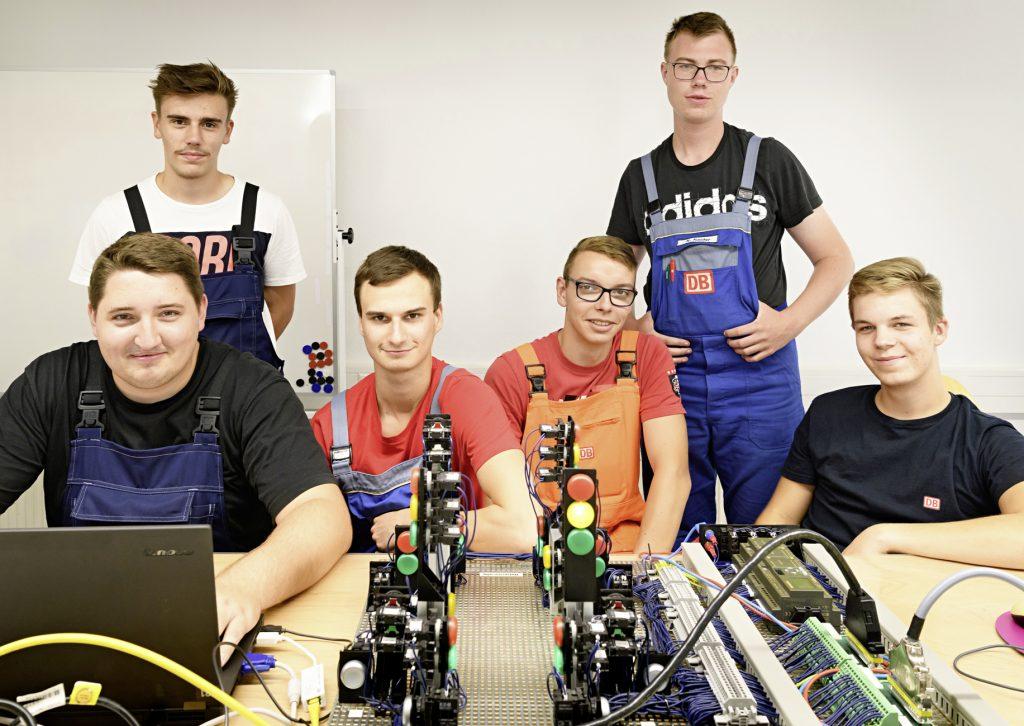 junge Männer in Arbeitskleidung vor Laptop und technischen Gerätschaften