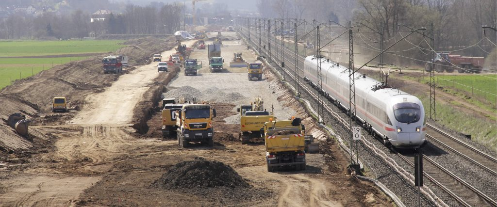 Baufahrzeuge neben einem Bahngleis mit ICE