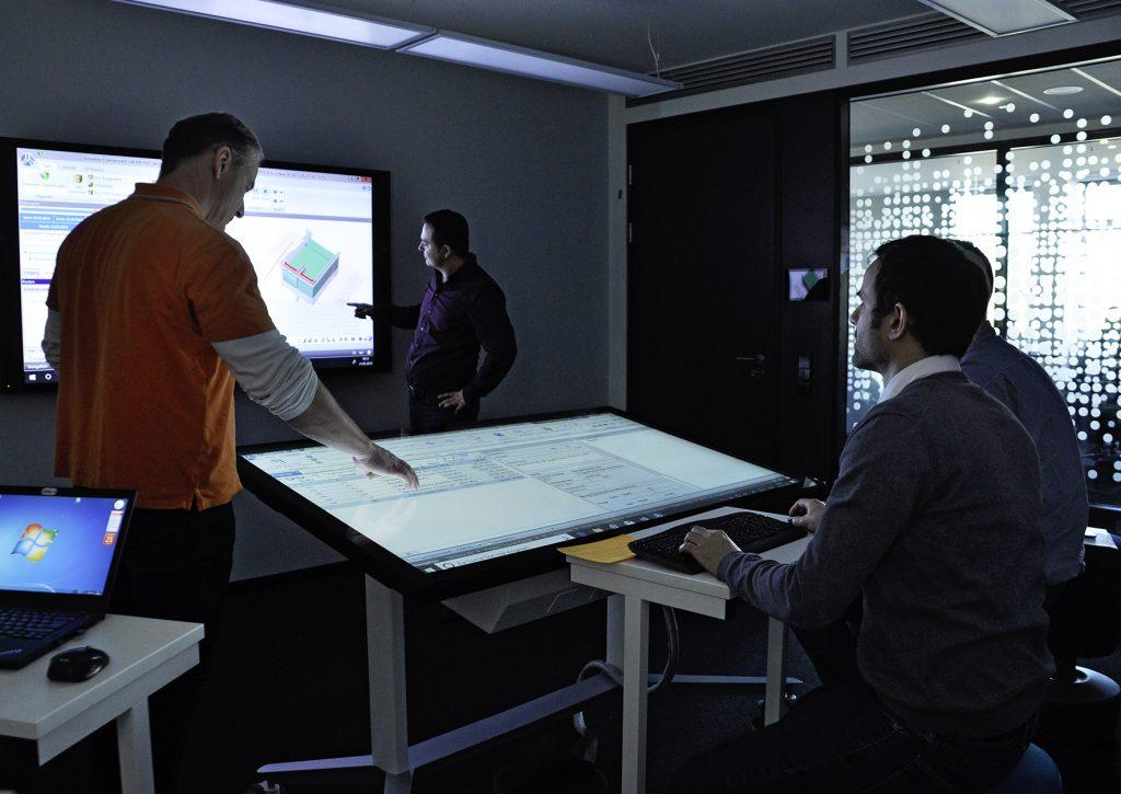 Personen bei der Planung am großen Wand-Bildschirm und Stelltisch ähnlichem Bildschirm