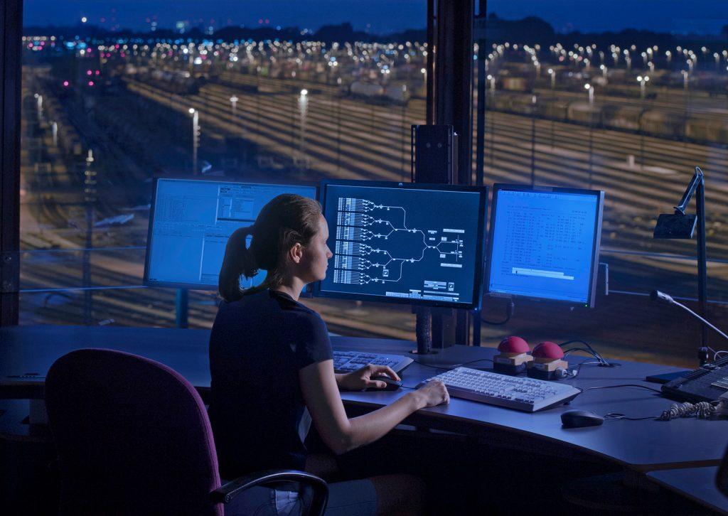 Mitarbeiterin in Stellwerk vor drei Bildschirmen im Rangierbahnhof Maschen