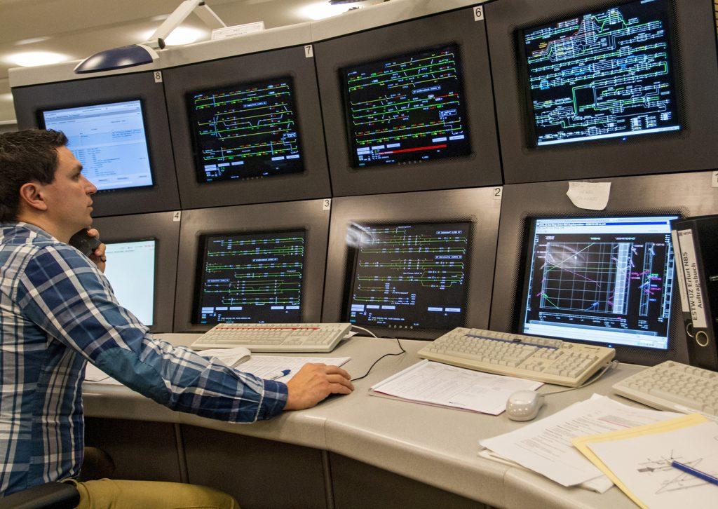Mitarbeiter in Stellwerk vor Bildschirmen