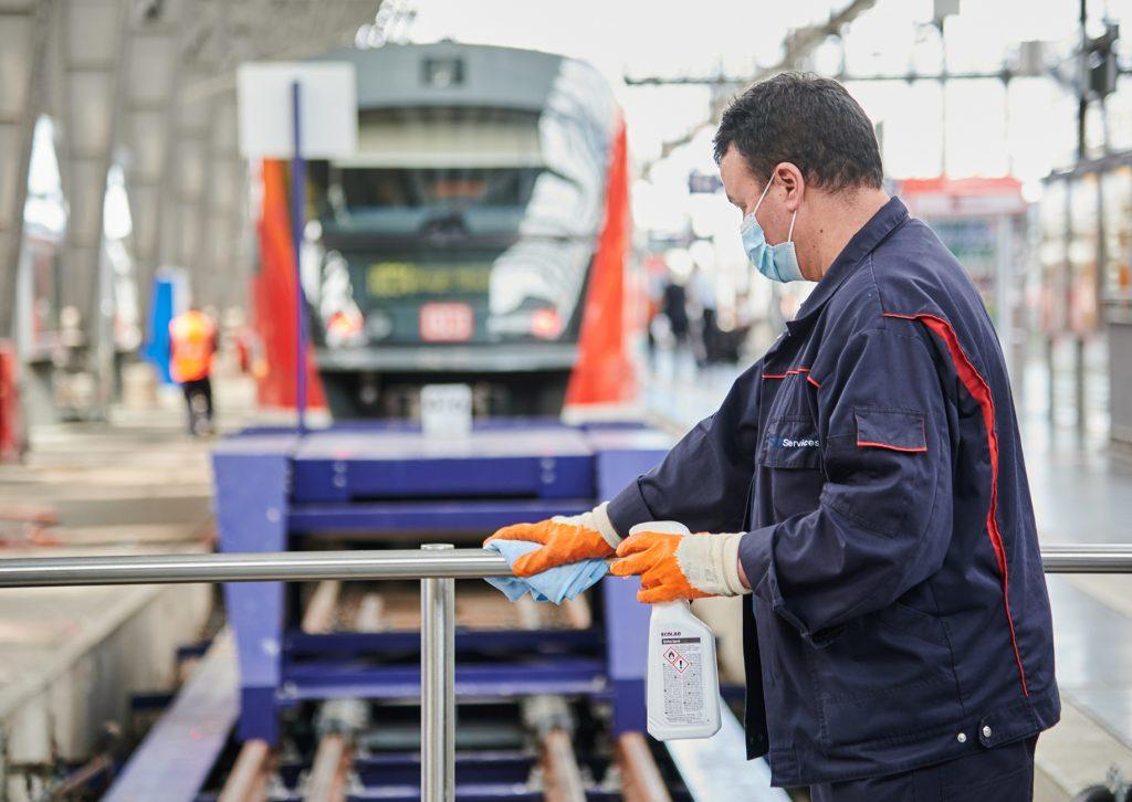 Mitarbeiter mit Mundschutz desinfiziert Geländer