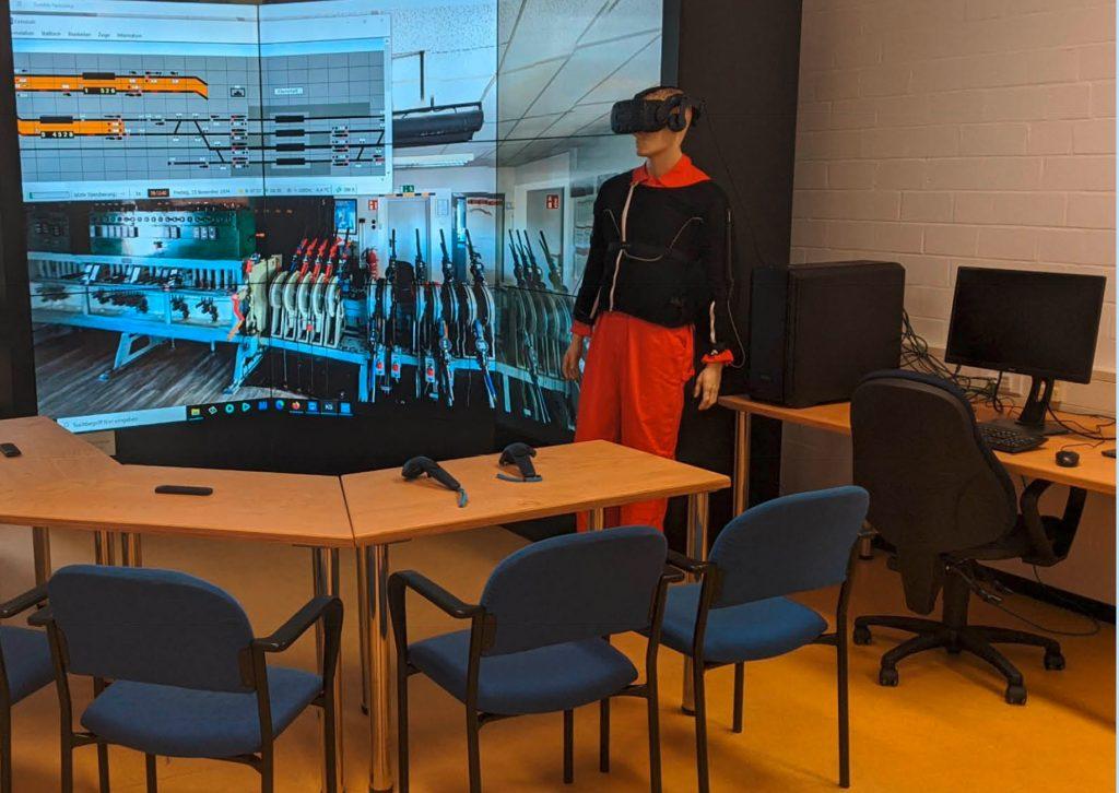 Menschliche Puppe mit VR-Brille vor einem Bildschirm mit Stellwerkssimulation
