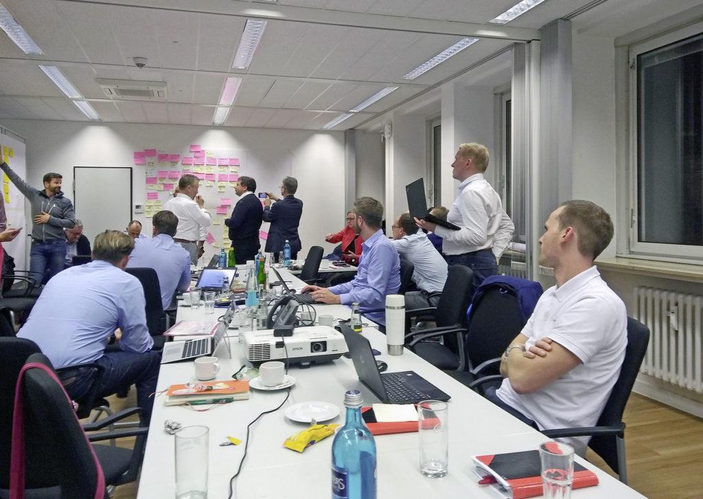 Mitarbeitende in einem großen Besprechnungsraum