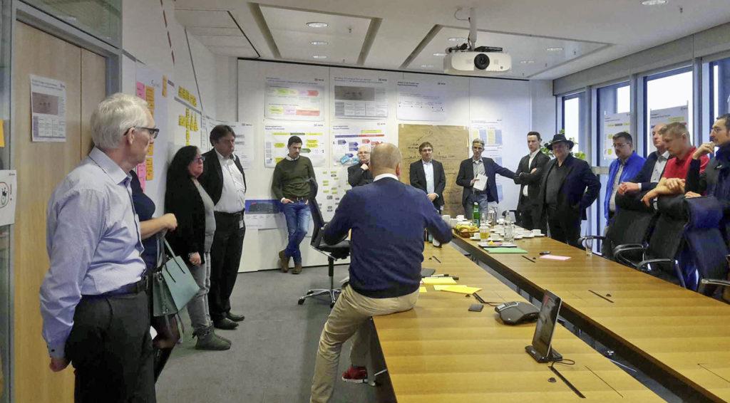 In einem Besprechungsraum sind Mitarbeitende bei einer Besprechung