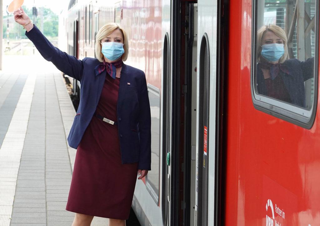 Mit Mund-Nasen-bedeckung: Kundenbetreuerin im Nahverkehr (KiN) gibt das Abfahrsignal
