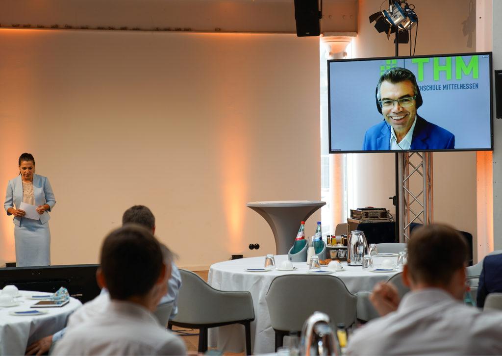 Moderatorin vor Publikum und Referent auf einem Bildschirm