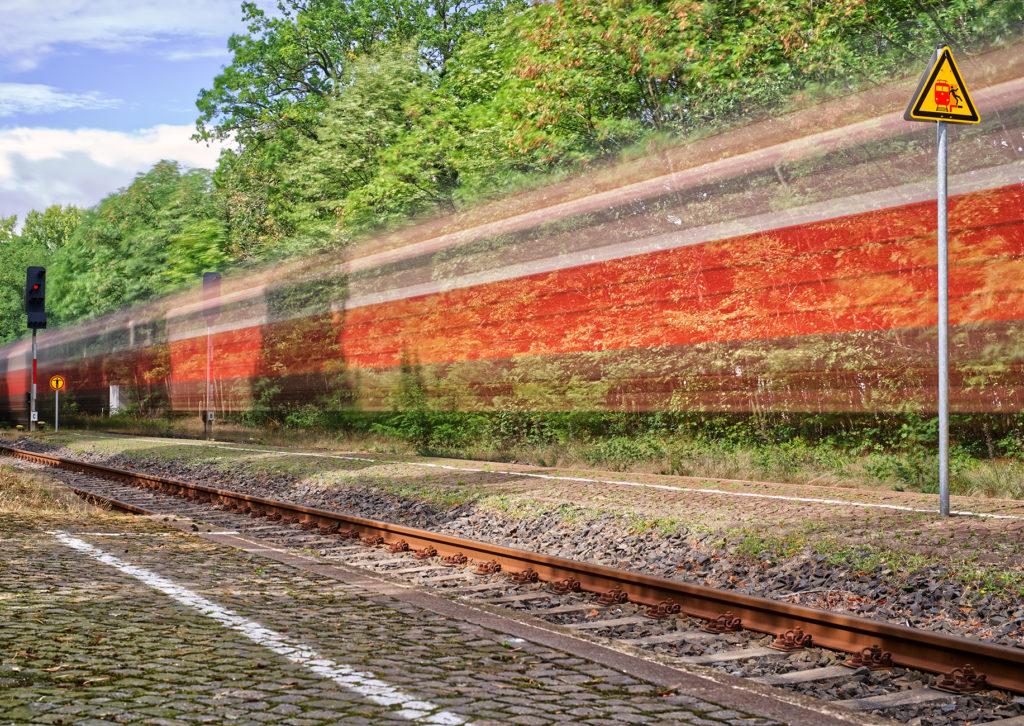 Vorbeifahrender Zug auf freier Strecke mit Bewegungsunschärfe