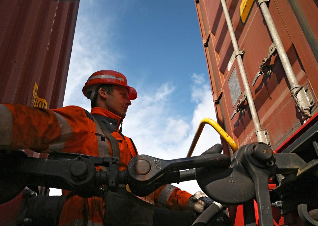 Mitarbeiter in Arbeitskleidung beim Kuppeln von Güterwagen