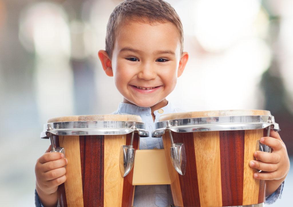 kleiner Junge mit Trommel und freudigem Gesichtsausdruck