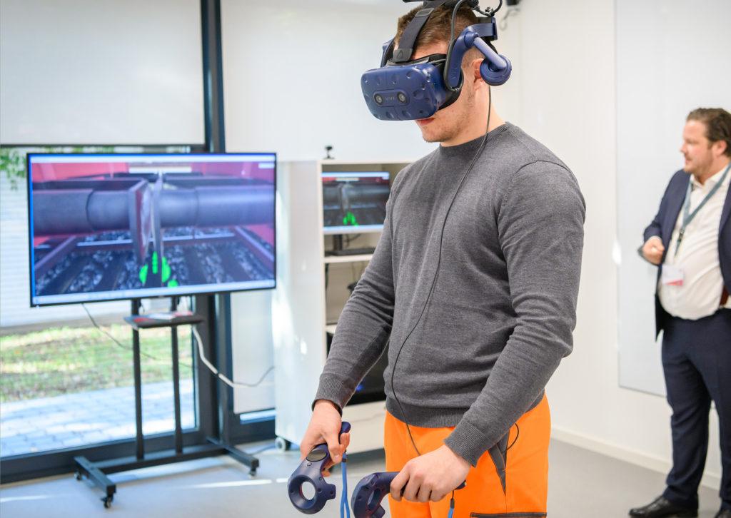 Mann mit VR-Ausrüstung vo einem Bildschirm