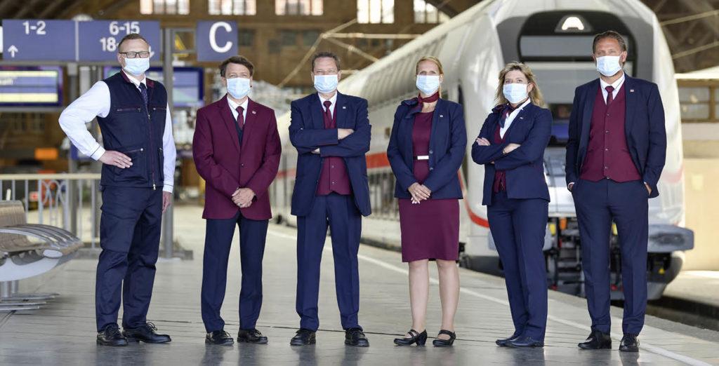 Mitarbeiter/-innen mit Mund-Nasenschutz auf einem Bahngleis