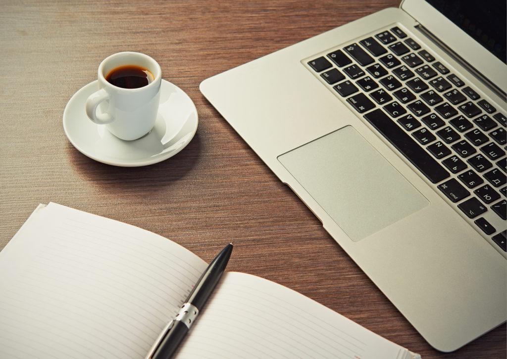 Schreibtisch mit einer Tasse Kaffee Computer Laptop, Notizbuch, Stift