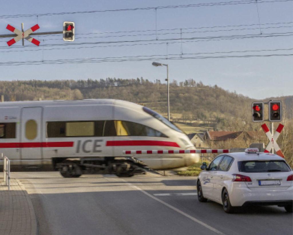 ICE fährt am geschlossenen Bahnübergang mit wartendem PKW