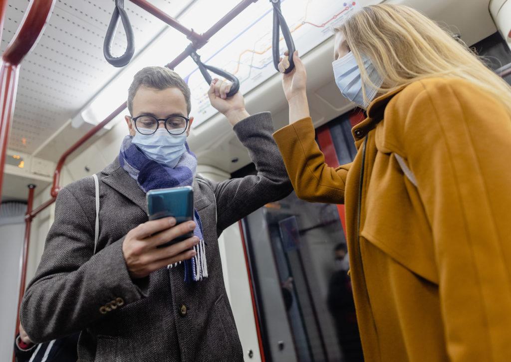 Fahrgäste in Nahverkehrszug mit Mund-Nase-Bedeckung
