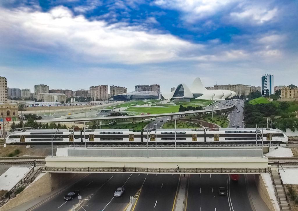 Ein Zug vor dem Hintergrund der Stadtkulisse von Baku
