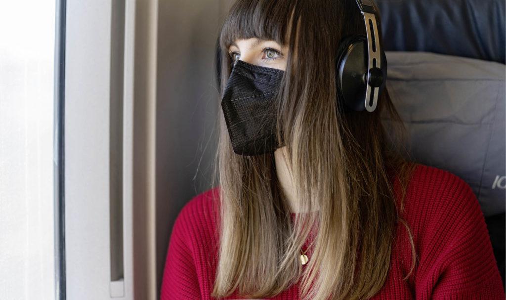 Frau mit Maske im Zug