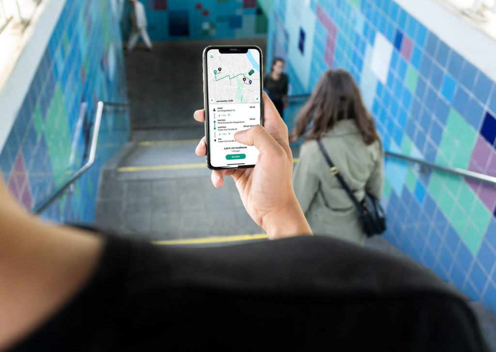 Person mit Smartphone und ioki-App auf einer Treppe