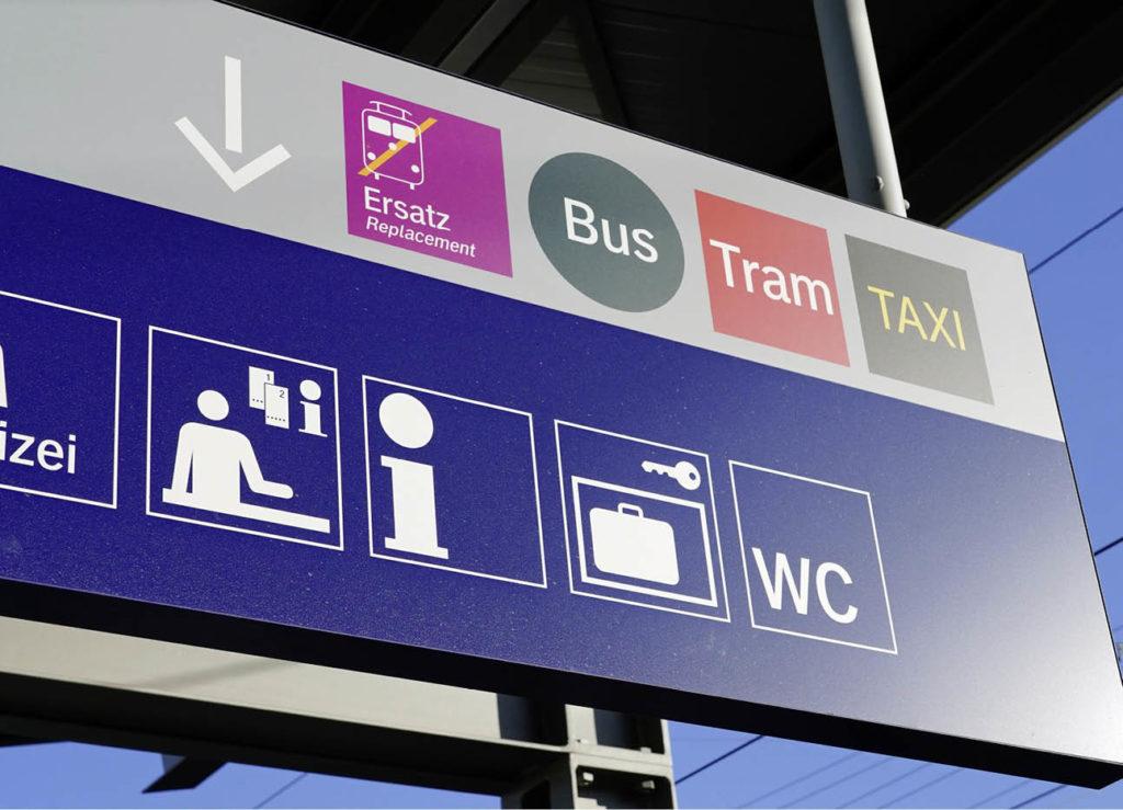 Hinweisschild mit verschiedenen öffentlichen Verkehrsmitteln an einer S-Bahn-Haltestelle