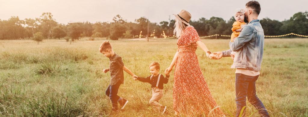 junge Familie mit drei kleinen Kindern auf einer Wiese