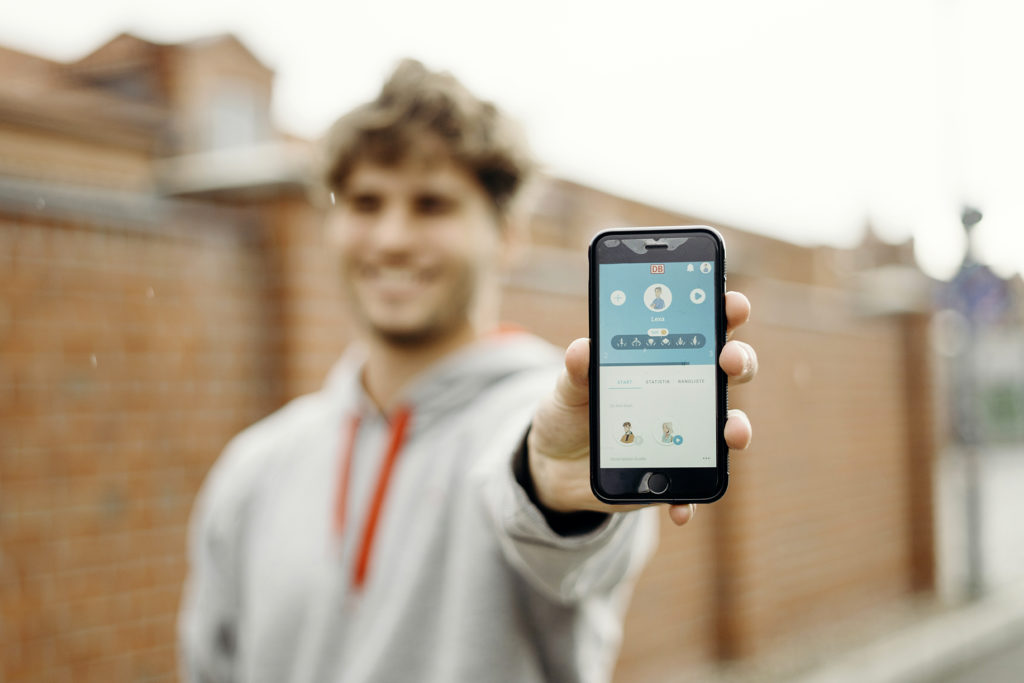 junger Mann zeigt Smartphone mir der APP