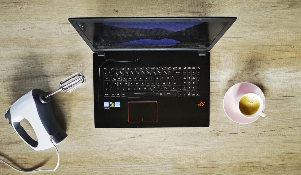 Laptop, Kaffeetasse und Haushaltsgerät