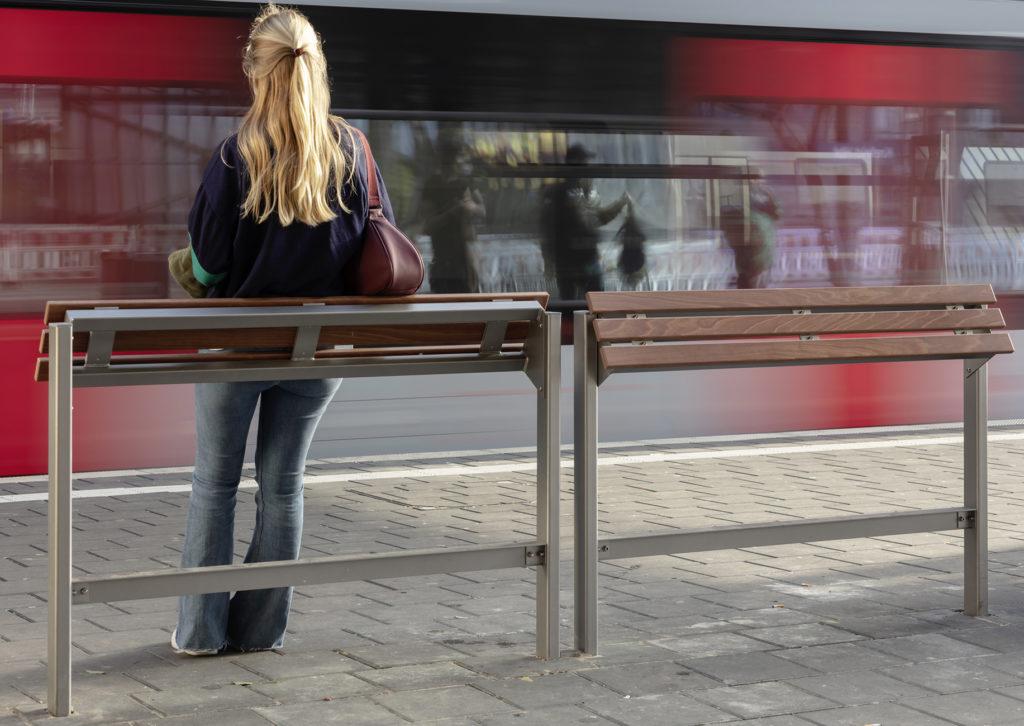 Frau am Bahnsteig an Stehhilfe, Zug fährt vorbei