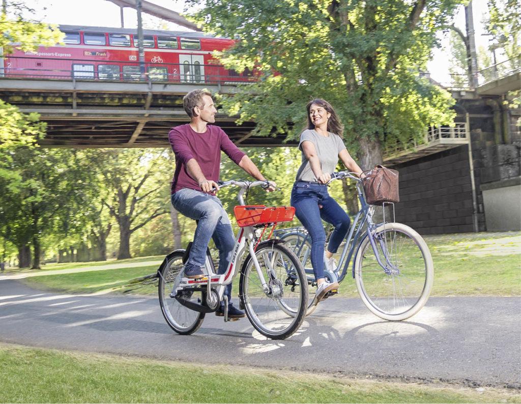 2 Personen auf Rädern fahren unter Bahnbrücke auf dem Radweg