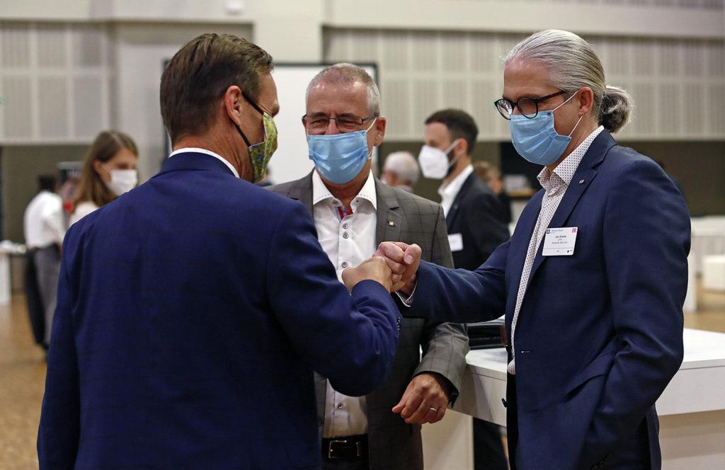 Menschen mit Maske begrüßen sich per Faust