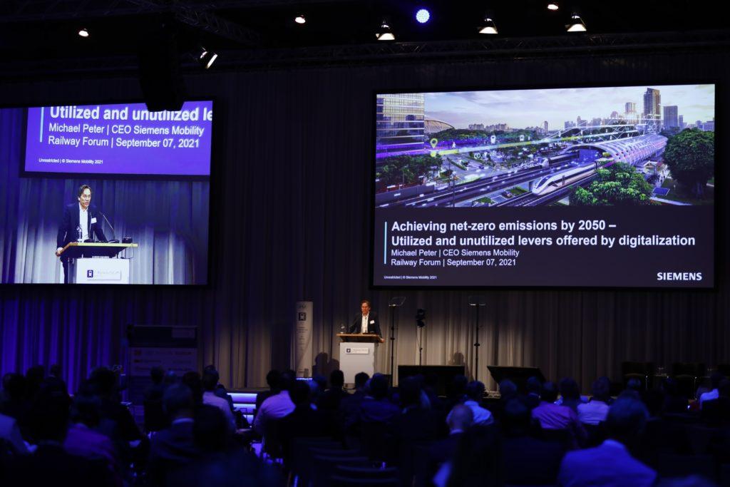 Redner auf Podium mit Präsentation im Hintergrund